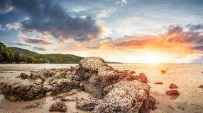 在沙子和日落的岩石与一朵好的云彩 免版税库存照片