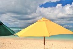 在沙子和蓝色和多云天空的一把黄色沙滩伞作为背景 库存图片