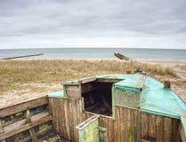 在沙子困住的被放弃的被击毁的小船 在含沙岸的老木小船 库存图片