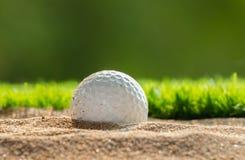 在沙子地堡的高尔夫球在草坪附近 免版税库存照片