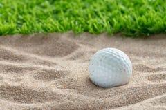 在沙子地堡的高尔夫球在草坪附近 库存图片