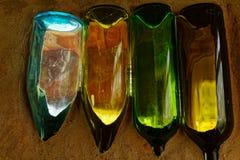 在沙子埋置的不同的色的酒瓶 免版税库存图片
