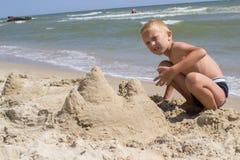 在沙子城堡的男孩修造 免版税图库摄影