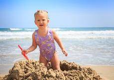 在沙子堆的小的白肤金发的女孩立场在海滩特写镜头微笑 免版税库存照片