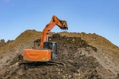 在沙子堆的橙色挖掘机与一个被上升的桶的 库存图片