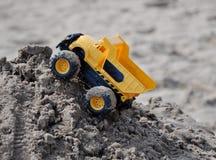 在沙子堆的玩具卡车 免版税库存图片