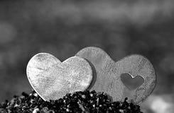 在沙子小山的两心脏在一个多岩石的海滩 免版税图库摄影