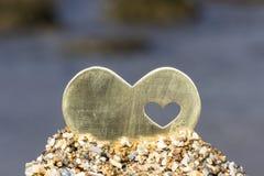 在沙子小山的心脏在一个多岩石的海滩 免版税库存照片