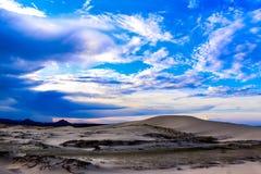 在沙子小山的蓝天 免版税库存图片
