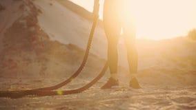 在沙子小山附近的运动的妇女训练在日落击中在地面上的绳索并且培养了尘土 影视素材