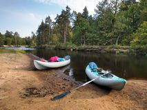在沙子岸的两艘皮船在森林的背景有桨和事的 库存图片
