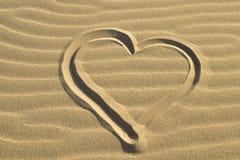 在沙子摘要背景中画的心脏 免版税库存照片