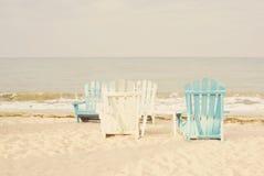 在沙子海景的白色和蓝色海滩睡椅和明亮的天空在暑假放松 设色葡萄酒的过滤器,太阳阴霾,强光 免版税库存照片