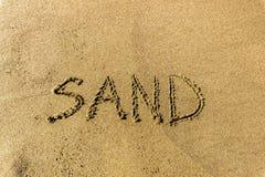 在沙子海滩写的沙子文本 库存照片