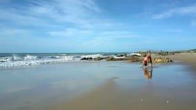 在沙子海滩女孩的泡沫似的波浪卷在瑜伽姿势站立 股票录像