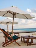 在沙子海滩的海滩睡椅和伞 免版税图库摄影