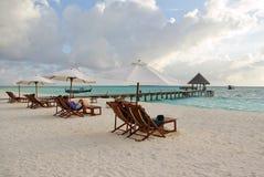 在沙子海滩的海滩睡椅和伞 免版税库存图片