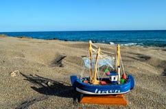在沙子海滩的玩具小船 库存图片