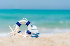 在沙子海滩背景的Lifebuoy与海星和渔船,拷贝空间 库存照片