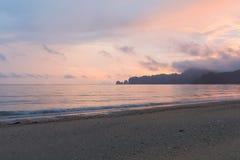在沙子海滩海岸地平线的日出口气 免版税库存照片