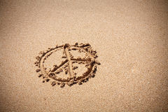 在沙子海滩的和平标志 免版税库存照片