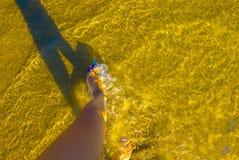 在沙子海滩的女性腿在海附近 免版税库存图片