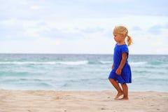 在沙子海滩的小女孩步行 免版税库存图片