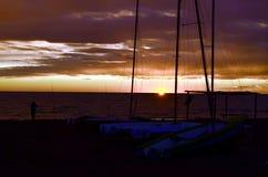 在沙子海滩的小船在日落期间 库存图片