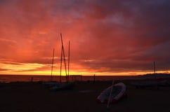 在沙子海滩的小船在日落期间 免版税库存照片