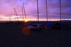 在沙子海滩的小船在日落期间 免版税库存图片