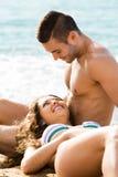 在沙子海滩的微笑的夫妇 免版税库存图片