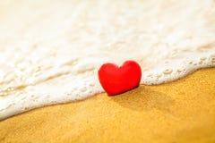 在沙子海滩的心脏与软的波浪温暖的光 库存图片