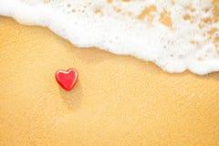 在沙子海滩的心脏与软的波浪温暖的光 免版税图库摄影