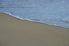 在沙子海滩的波浪 免版税库存图片