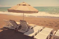 在沙子海滩的海滩睡椅 图库摄影