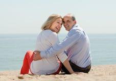 在沙子海滩的爱恋的成熟夫妇 免版税库存照片