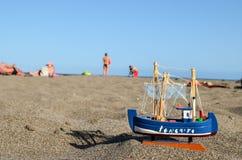 在沙子海滩的玩具小船 免版税库存照片