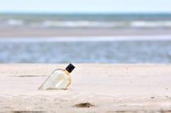 在沙子海滩的瓶 库存照片