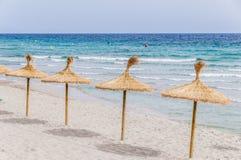 在沙子海滩的秸杆伞 库存照片