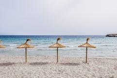 在沙子海滩的秸杆伞 免版税图库摄影