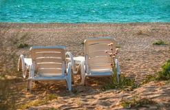 在沙子海滩的轻便折叠躺椅 免版税图库摄影