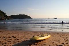 在沙子海滩的黄色冲浪板与海、蓝天和一座山在背景 库存照片