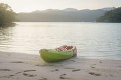 在沙子海滩的绿色和橙色皮船 免版税库存图片