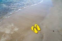 在沙子海滩的黄色拖鞋 免版税库存图片