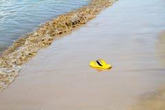 在沙子海滩的黄色拖鞋 免版税库存照片