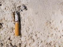 在沙子烟灰缸的一根香烟 免版税库存图片