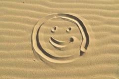 在沙子画的面带笑容 库存图片