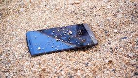 在沙子的一个手机 库存图片