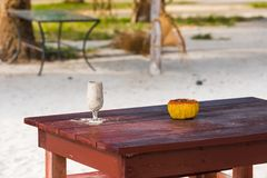在沙子的一块玻璃在桌,巴拉德罗角,马坦萨斯,古巴上 复制文本的空间 免版税库存照片