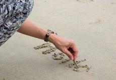 在沙子的一夫人` s手文字词`你好`在海滩 库存图片